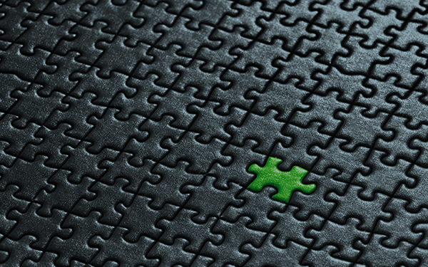 black puzzle with one green piece